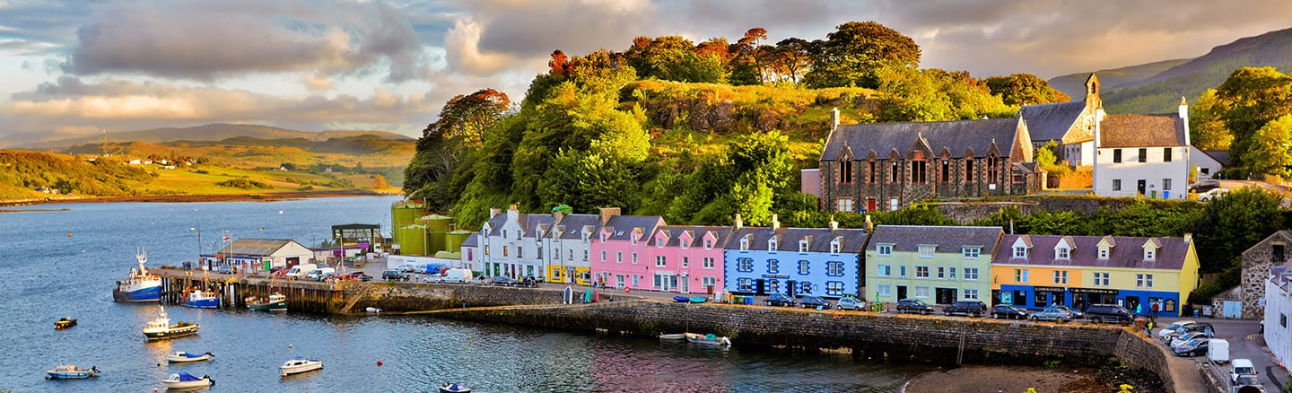 Pastel painted builings surround Portree harbour where fishing boats lie at anchor