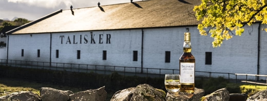 A glass and bottle of Talisker Malt Whisky placed on a wall outside the white-washed buildings of Talisker Distillery