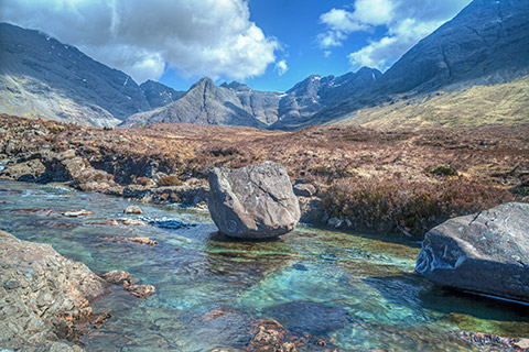 The bright blue water of the Fairy Pools flow through heather-clad moorland with the Cuillin Mountains in the background