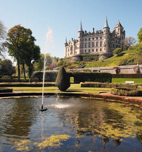 Looking up from the pond and water-feature of the formal gardens to cliff-top turreted Dunrobin Castle