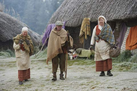Guides dressed in traditional highland clothes walk past the thatched cottages of the Highland Folk Museum