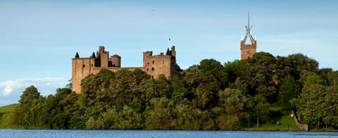The modern steeple of St Michael's church and the ruins of Linlithgow Palace seen from the banks of the pretty loch