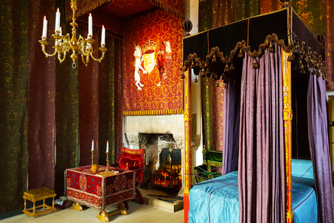 The sumptious Royal Apartments containing a four-poster bed and an ornate desk and chair in front of a fireplace