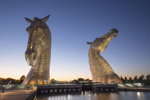 The flood-lit Kelpies horse-head statues at night time seen from the canal bank