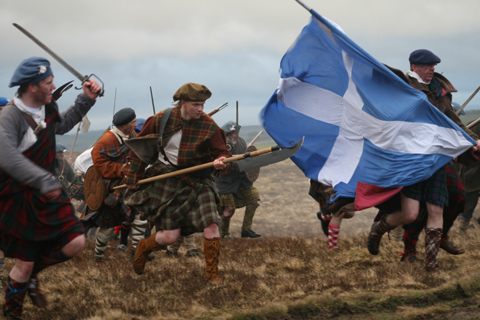 Highlanders dressed in kilts and carrying swords recreate a charge during the Battle of Culloden