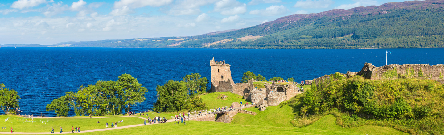 Summer view of Urquart Castle overlooking the bright blue waters of Loch Ness