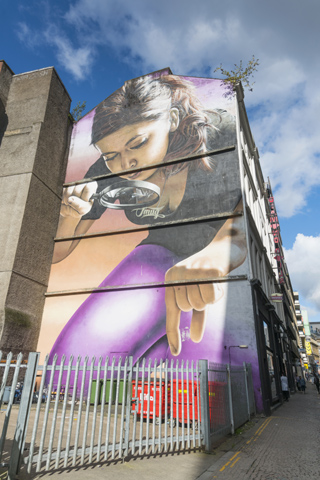 Mural painting of a woman with a magnifying glass trying to pick something up from the ground