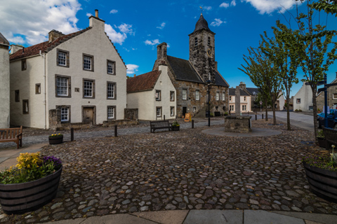 Culross clocktower and Mercat Cross seen across a cobbled square