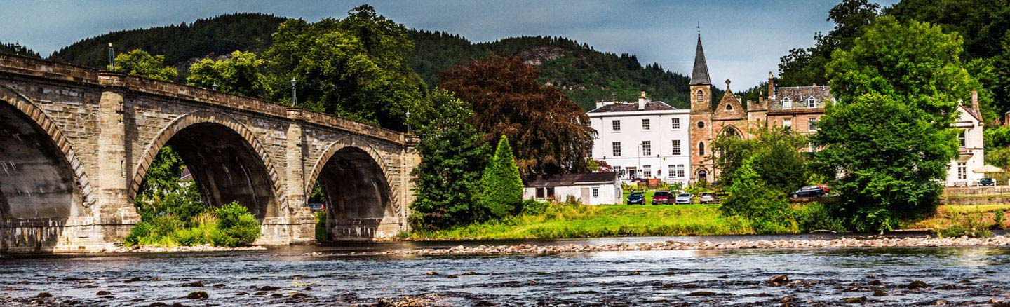 White painted buildings of Dunkeld seen across the tumbling waters of the River Tay