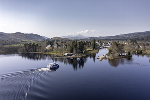Ariel view of a cruise boat arriving back in Fort Augustus from Loch Ness