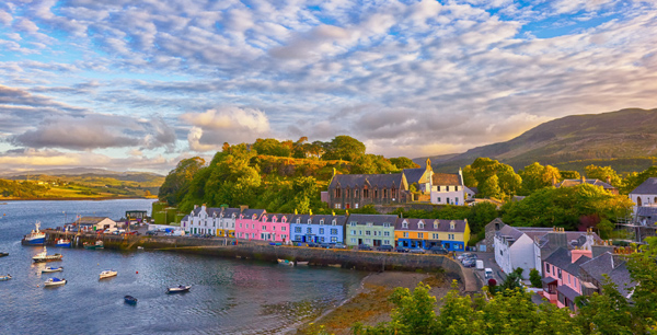 Portree harbour surrounded by colourful buildings seen at sunset