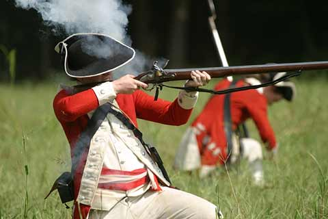 Redcoat soldier kneels as he fires a shotgun