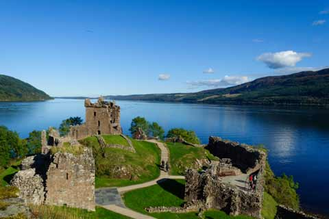 Summer view of the ruins of Urquart Castle overlooking the blue waters of Loch Ness