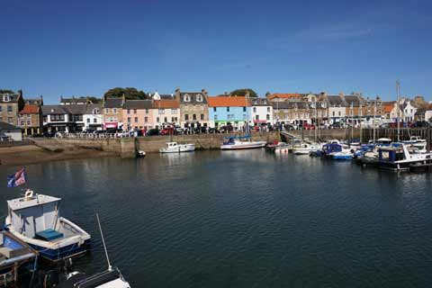 Colourful buildings overlook the boats in Anstruther Harbour on a sunny day