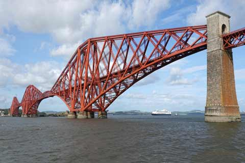 A cruise ship sits under the red painted Forth Rail Bridge
