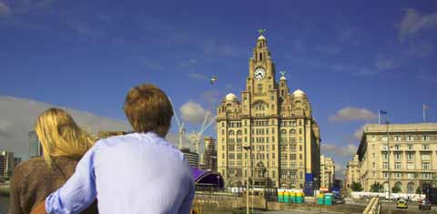 Couple view the Liverpool Waterfront from the deck of a ferry