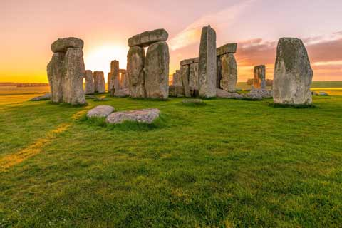 Sunrise at Stonehenge give a gentle view of the massive monolith stones