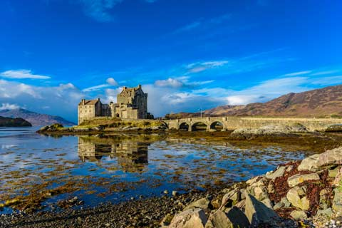 Eilean Donan Castle and the bridge to its little island seen from the banks of Loch Duich at low tide