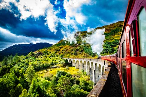 View along the side of the Jacobite Steam train to the locomotive as it crosses the Glenfinnan Viaduct heading towards Ben Nevis