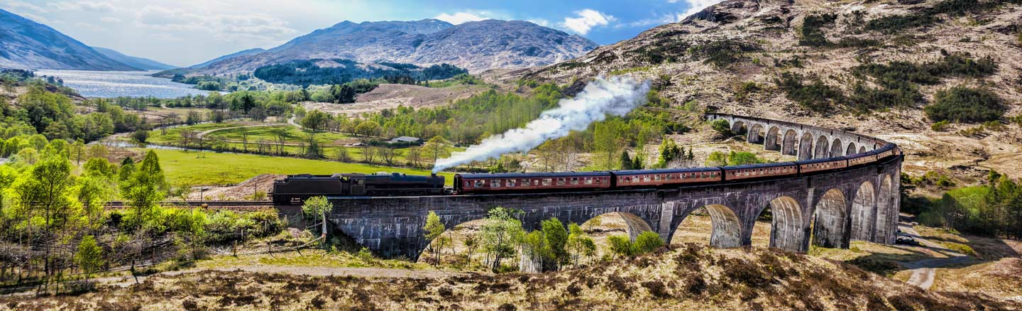 The Jacobite Steam Train crosses the Glenfinnan Viaduct with Loch Shiel in the background