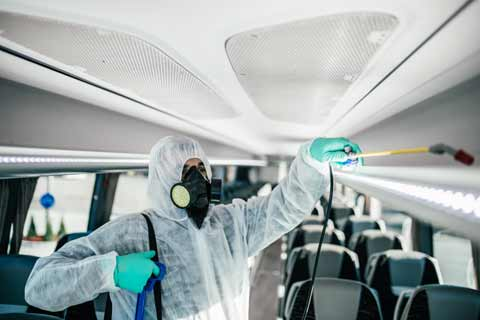 A cleaner wearing protective clothing sanitises the interior of a coach
