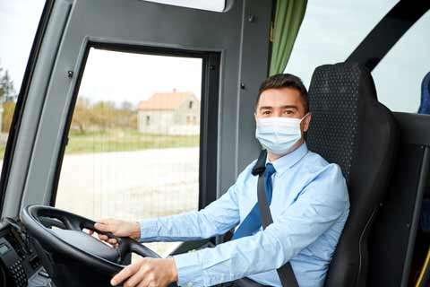 Friendly tour driver wearing a mask greets passengers on board