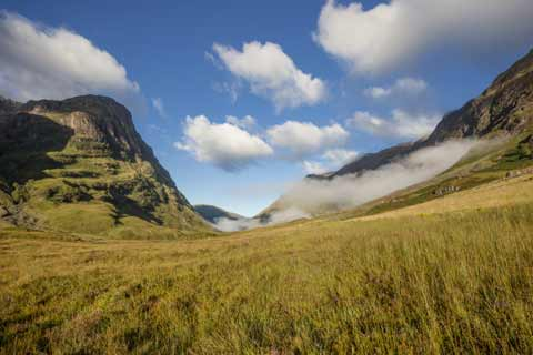Clouds swirl around the Three Sisters of Glen Coe mountain range