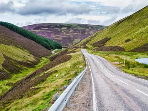 The Lecht Road makes its way through heather-clad mountains
