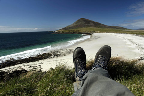 A walker rests at Northton beach, looking towards the hill of Ceapabhal on the Isle of Harris