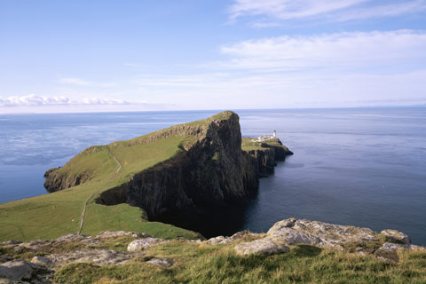Looking along the rugged coastline of Neist Point, Isle Of Skye, towards the white-washed lighthouse overlooking The Minch