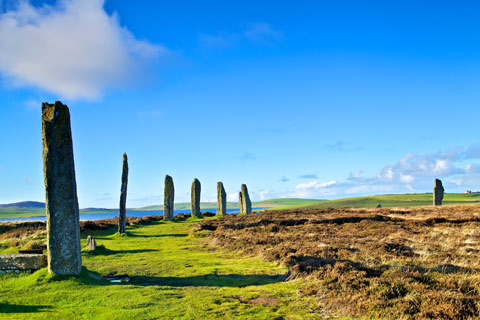 Seven standing stones of the Ring of Brodgar on Orkney under a bright blue sky with Loch Harray in the distance