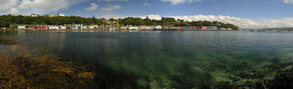 The colourful houses of Tobermory seen from across the crystal-clear waters of Tobermory Bay