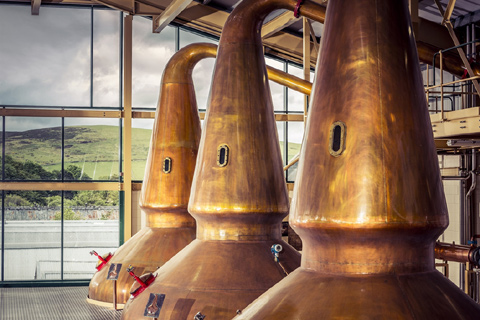 Three large copper stills housed in a glass-fronted building at Glenlivet Distillery