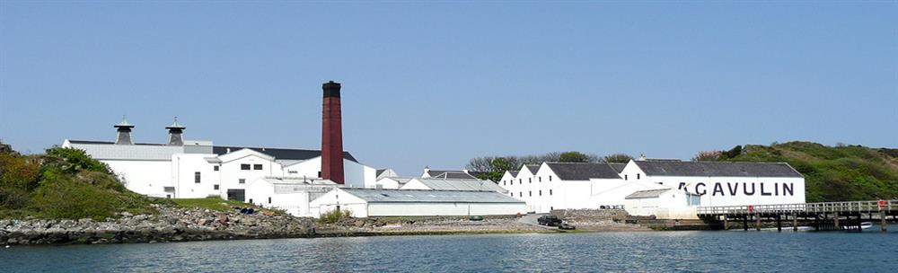 A waterside view of Lagavulin Distillery showing the whitewashed buildings, red-painted chimney and famous twin-pagodas