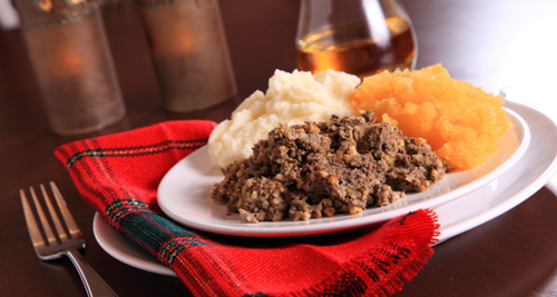 Traditional Haggis, Neeps and Tatties served by candle light on a tartan dressed table