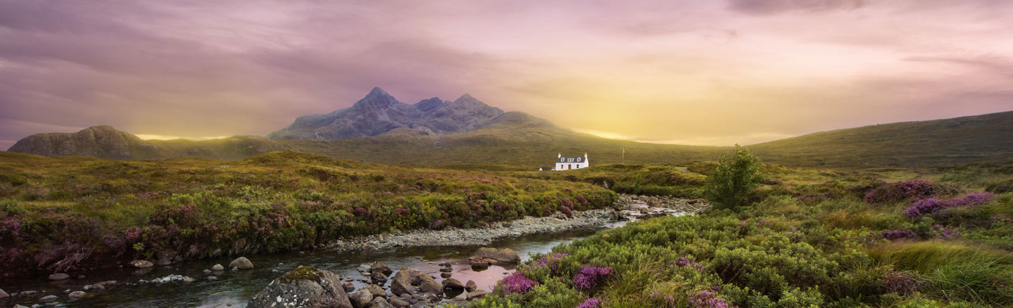 Lagangarbh Cottage sits by the River Coupal and is surrounded by heather with the mountains of Glen Coe in the background