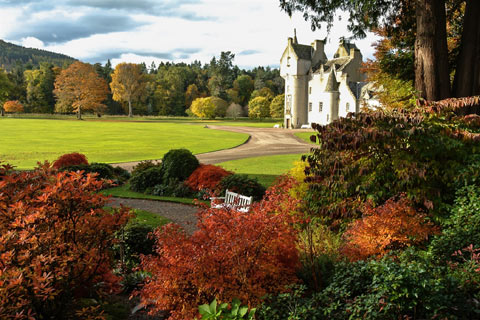 Autumn leaves contrast with the green lawn and blonde stonework of Ballindalloch Castle