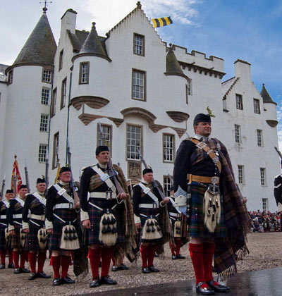 Atholl Highlanders standing to attention outside white-washed Blair Castle