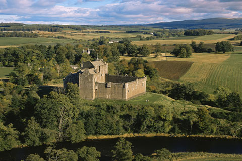 Medieval Doune castle sitting at an elevated position surrounded by woods at a bend of the River Teith