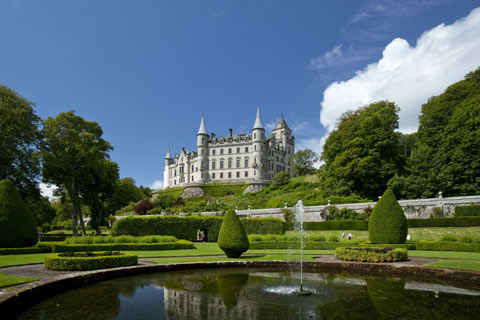 Fairytale Dunrobin Castle overlooking the formal gardens with a pond and waterfall in the foreground