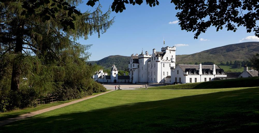 Looking through the trees towards white-washed Blair Castle with the Perthshire Hills in the background