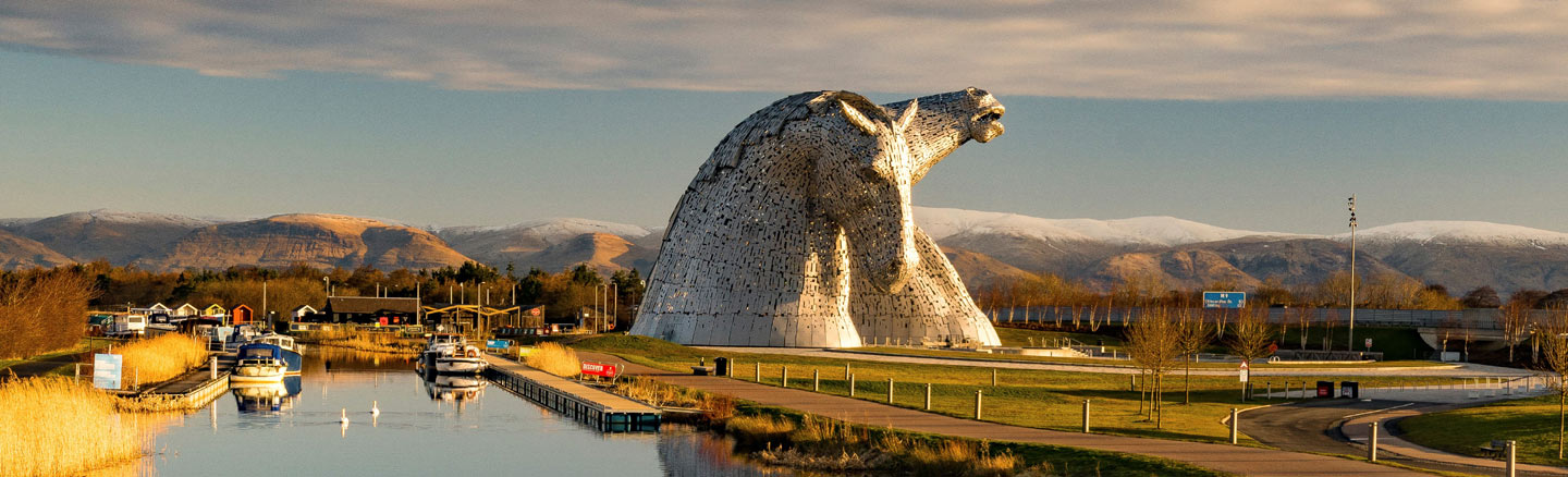 Kelpies horse-head statues towering above boats on the Forth and Clyde Canal