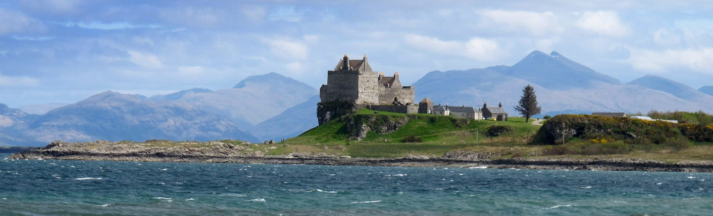 Cliff-top Duart Castle overlooking the Sound of Mull with mountains in the background