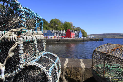 Colourful buildings overlook Tobermory Bay with lobster creels in the foreground