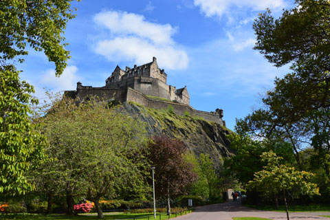 Edinburgh castle pictured sitting on rock amidst trees and flowers in Princes Street Gardens