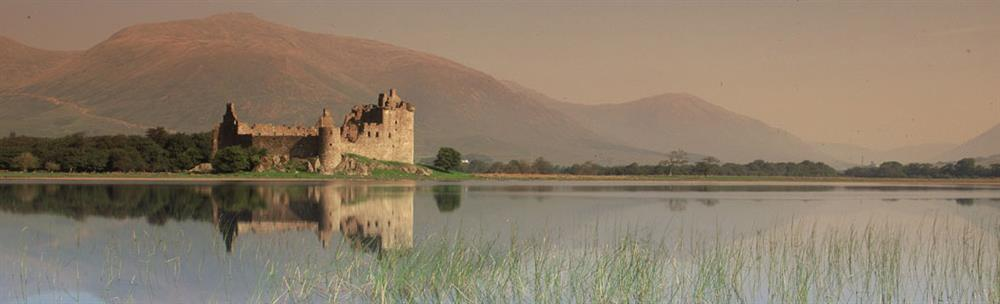 Picturesque ruins of Kilchurn Castle with mountains and sky in background, shown reflected in still water