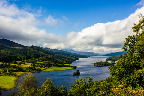 Trees, the clear water of Loch Tummel and blue sky with white clouds at Queen's View