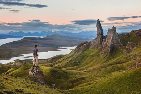 Man standing on small rock looking at the crags of the Old man of Storr on the Isle of Skye