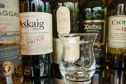 Close up of whisky glass with selection of Islay whisky bottles in background