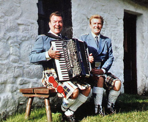 The Alexander Brothers seated in front of a white cottage wearing blue jackets and black, red and yellow kilts, one holding an accordion